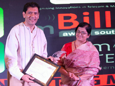 Rajesh Shah receiving the mBillionth trophy and plaque from Sudha Rao